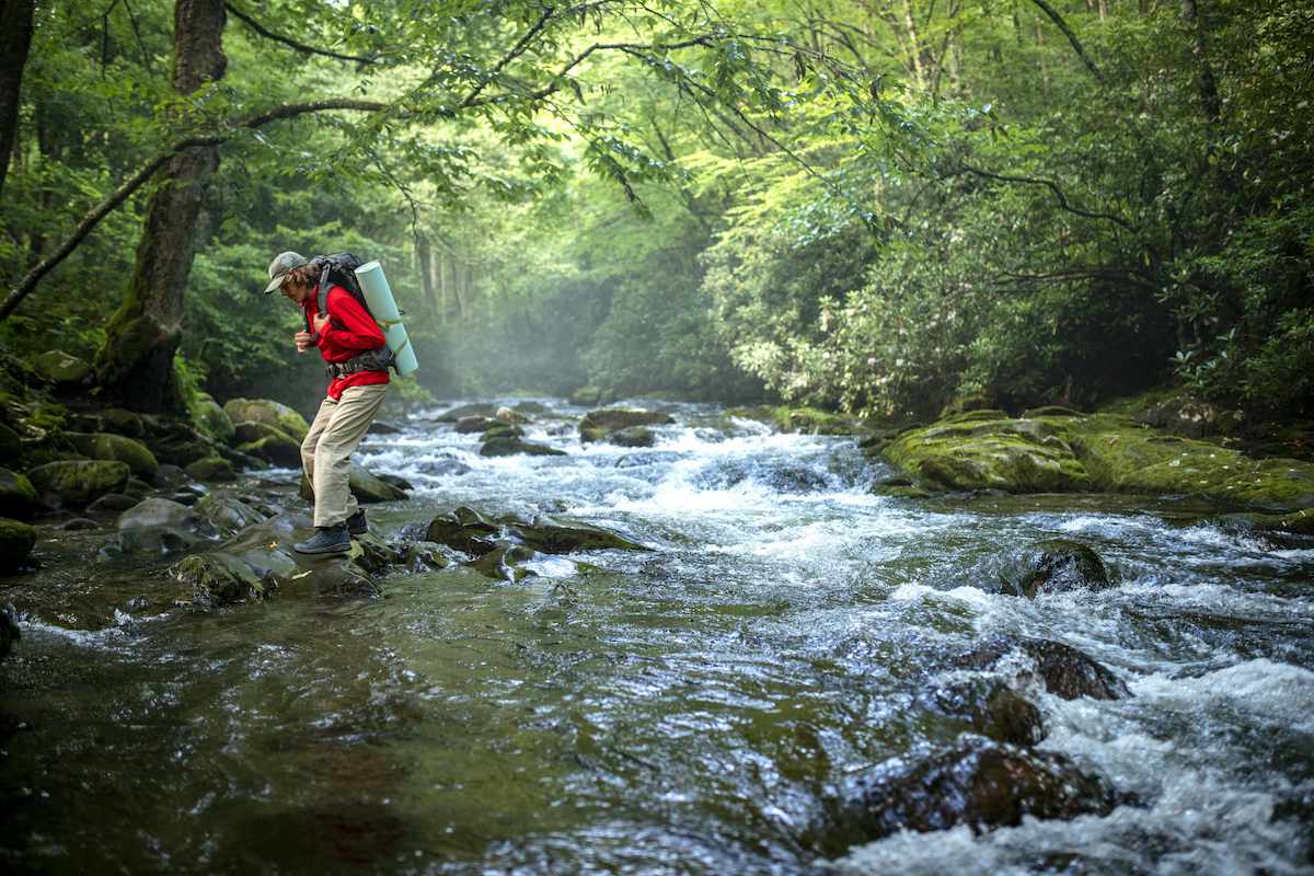 A hiker carefully crosses a stream in the middle of a forest