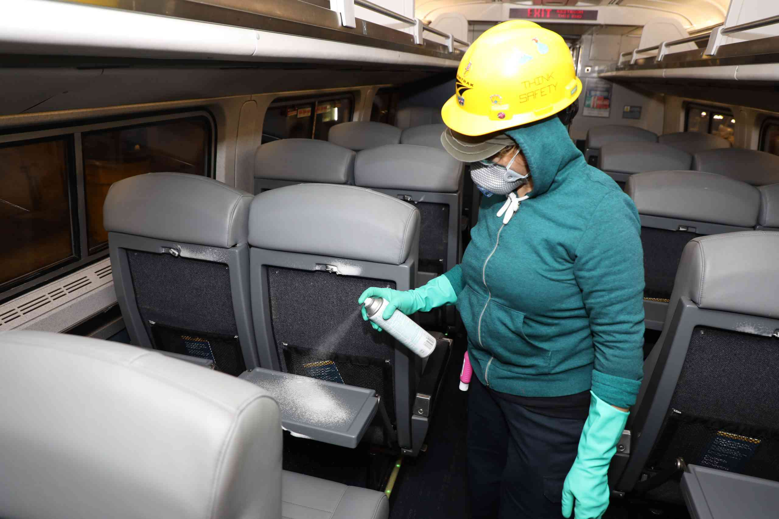 An employee spraying disinfectant on an Amtrak seat