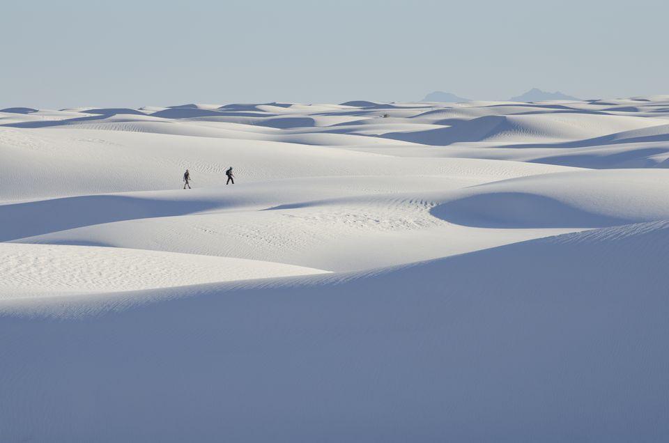 Personas distantes caminando sobre un paisaje nevado