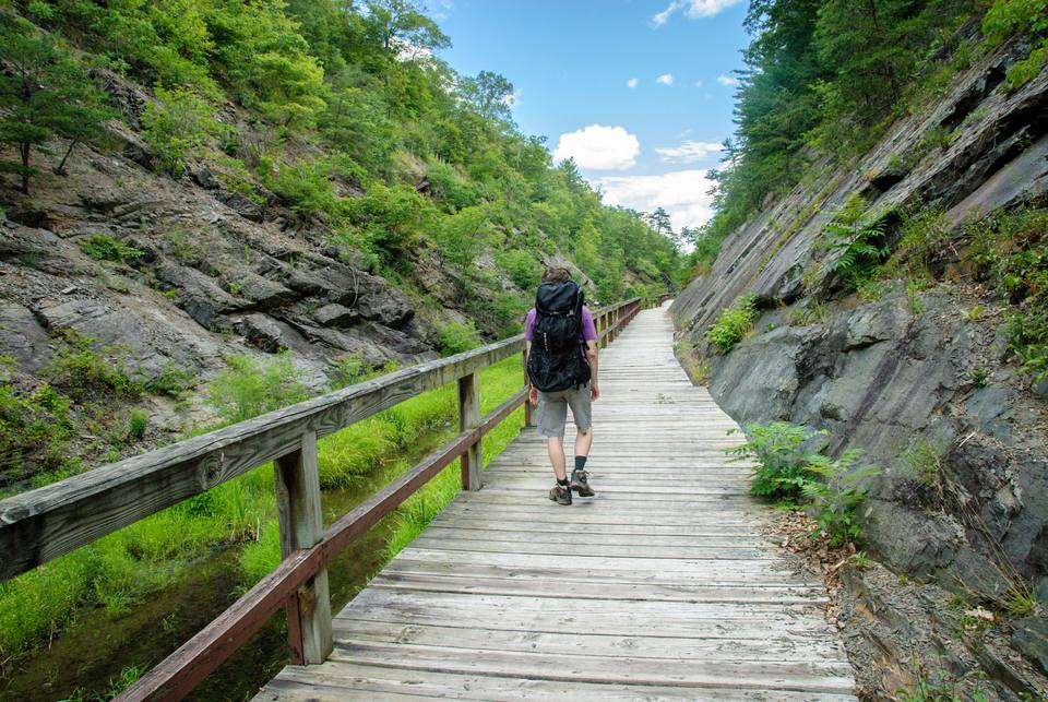 Person with a large backpack hiking on a path along the Chesapeake and Ohio Canal