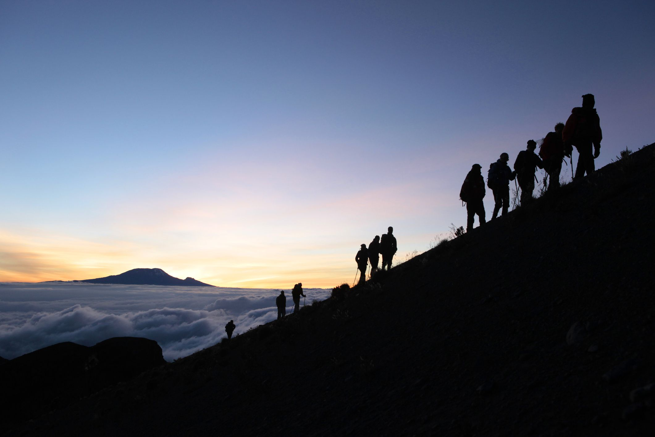 Hikers climbing Mount Meru with Mount Kilimanjaro in the background