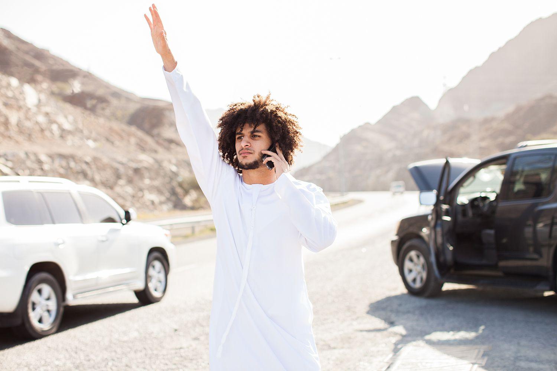 Man raising his hand on a road