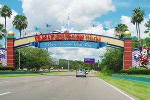 an entrance of Walt Disney World Resort. Some cars are visible.