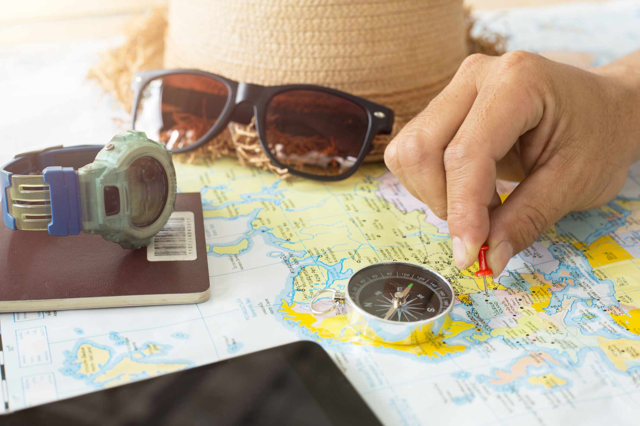 Hand putting a pin into a map with compass and sunglasses