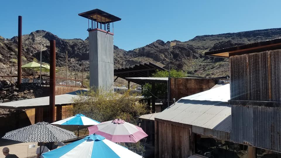 image of Corrugated metal structures with large table umbrellas in the bottom left corners and mountains in the background