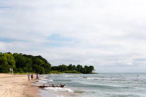 A few people walking down a white sand beach