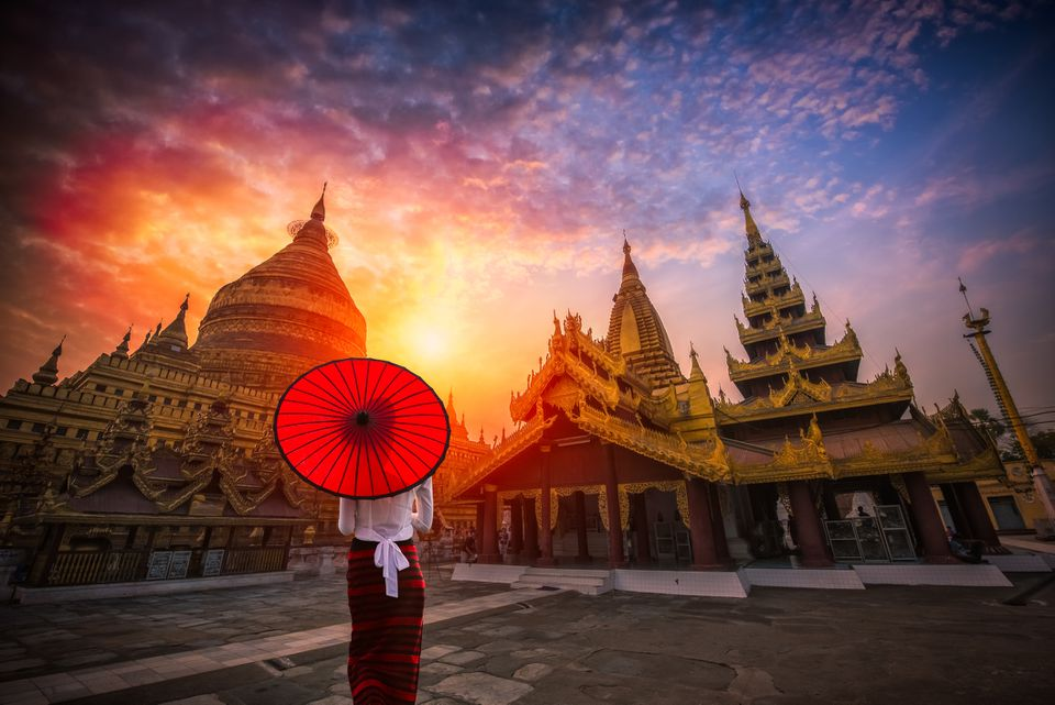 Burmese woman holding traditional red umbrella and looks at Golden Shwezigon pagoda in Bagan, Myanmar