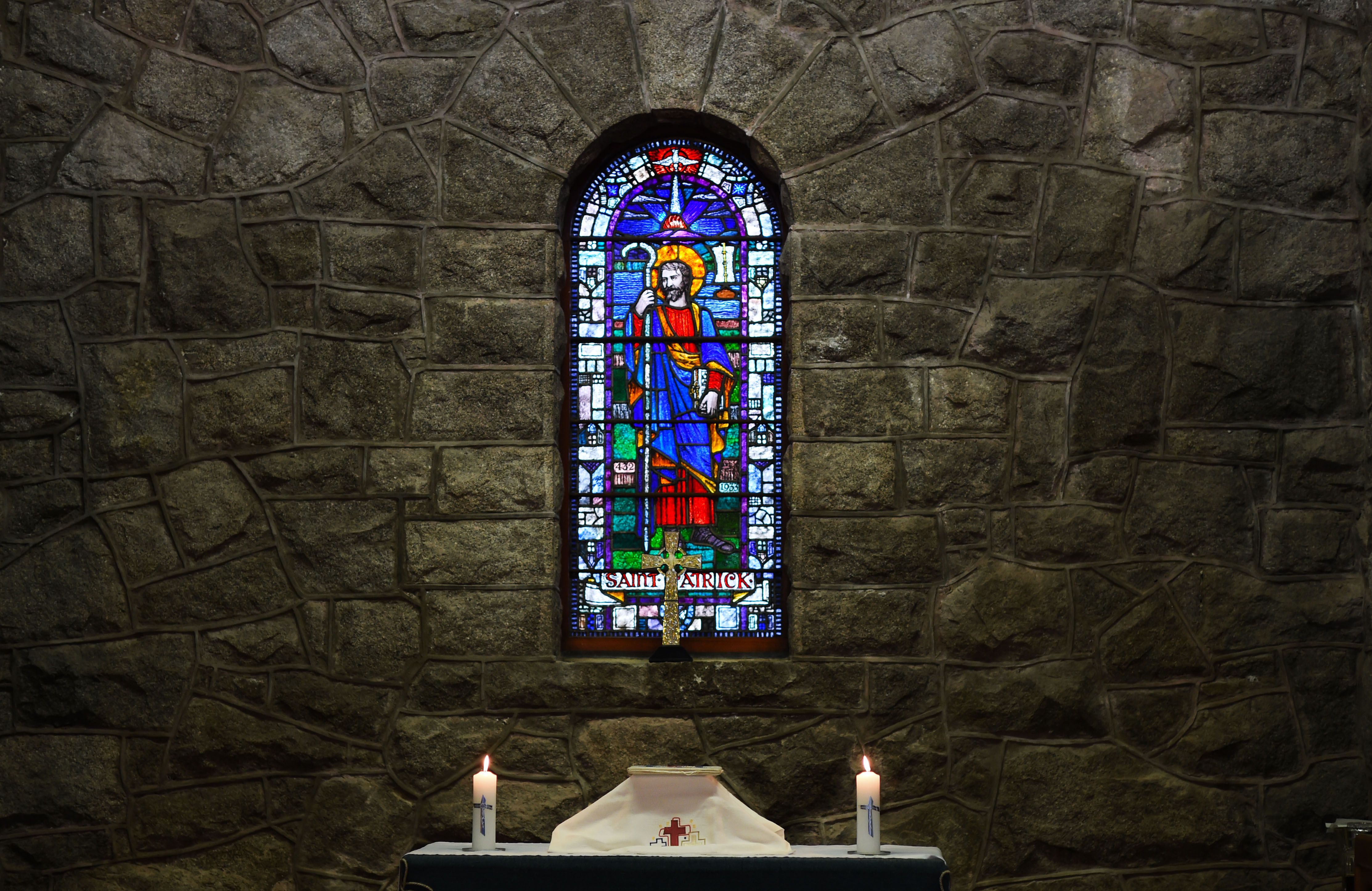The altar at Saint Patrick's Church with the stained glass window of Saint Patrick