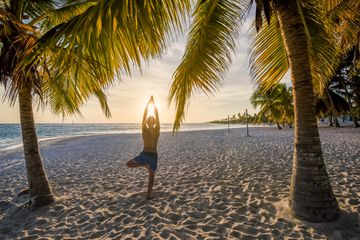 Man practicing yoga on a tropical beach at sunset in the Caribbean