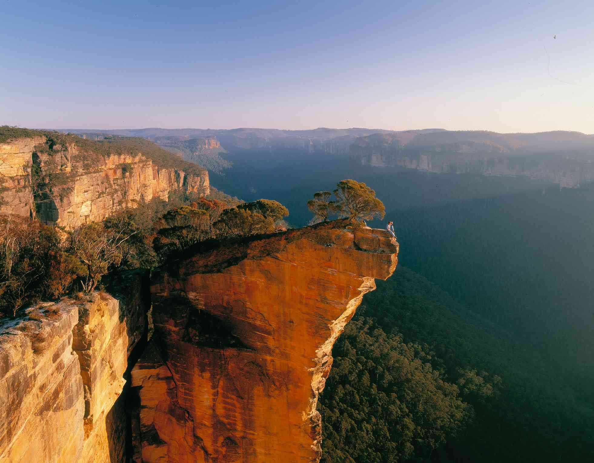 long person sitting on a cliff rock formation in the australian blue mountains