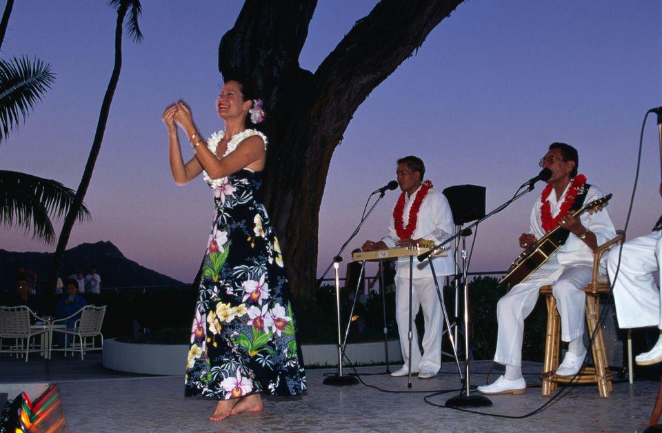 A hula dancer, with the Hawaiian trio The Islanders, at the Halekulani Waikiki.