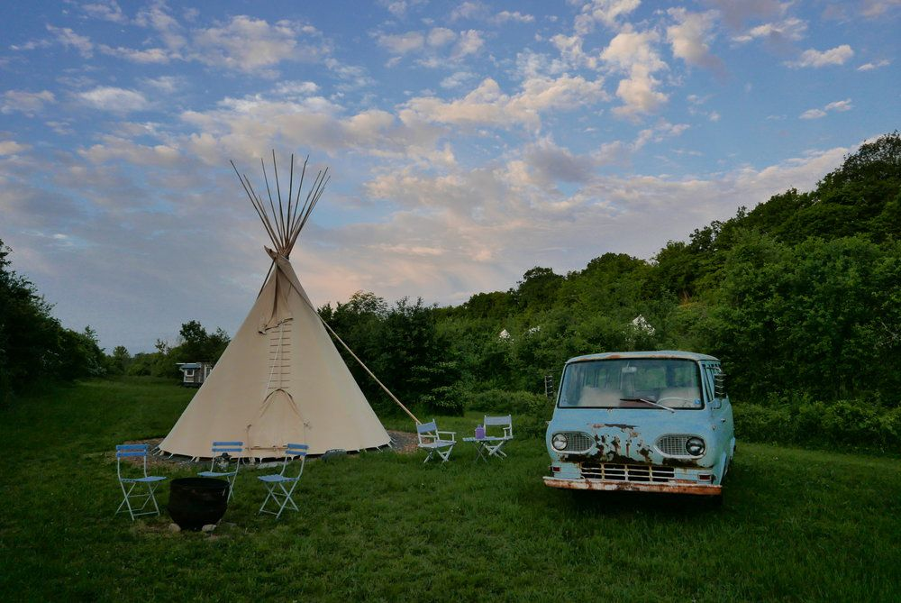 A yurt campsite beside an old van