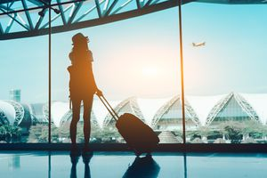 Silhouette Woman With Luggage Standing In Airport