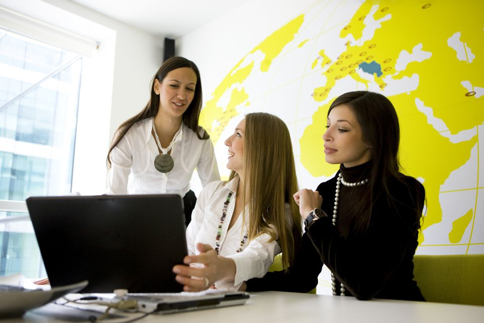 Women at a travel agency look at a computer near a large world map