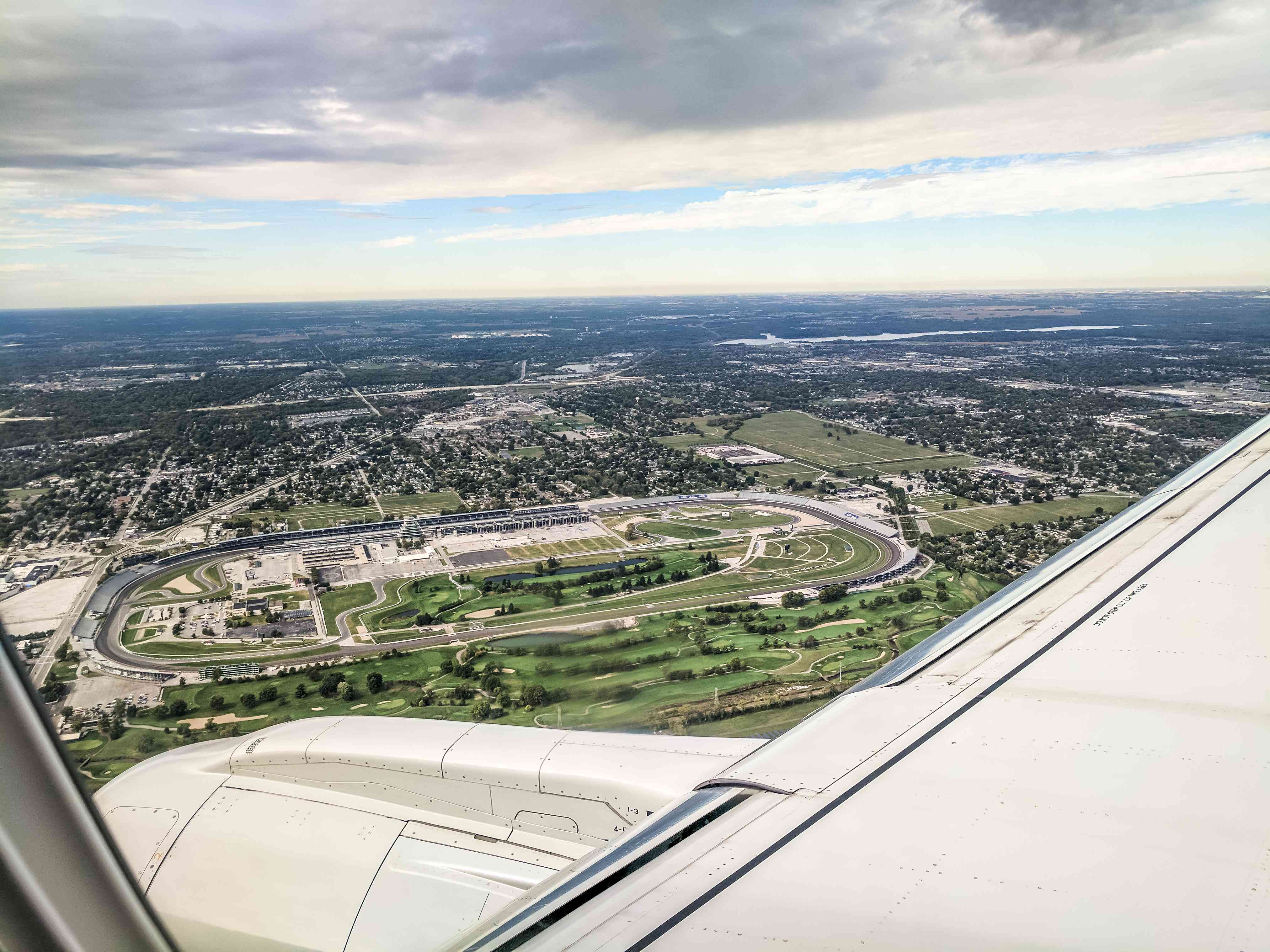 Aerial view of Indianapolis Motor Speedway with airplane wing