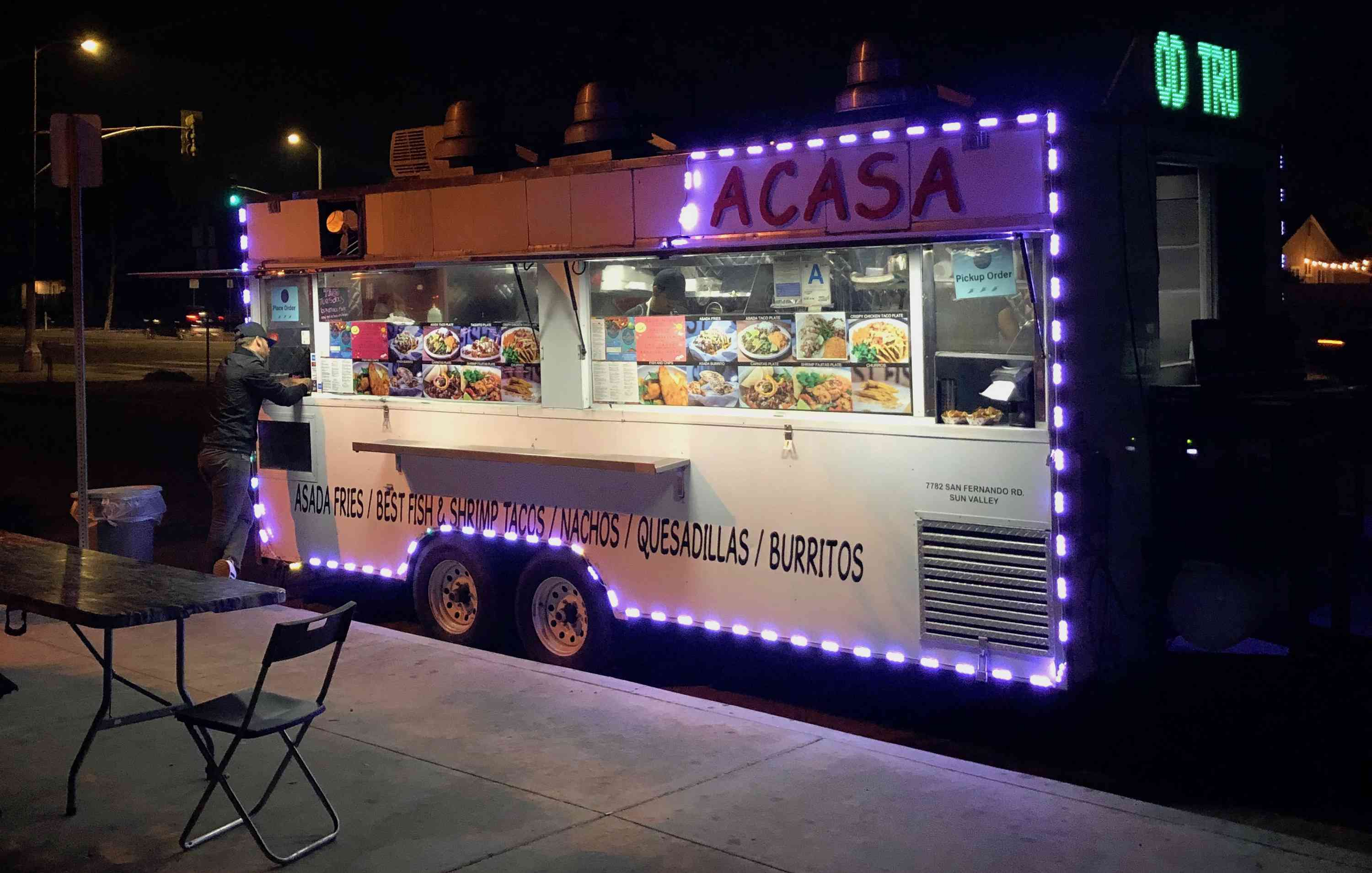 Acasa taco Truck at night with a person ordering from the window