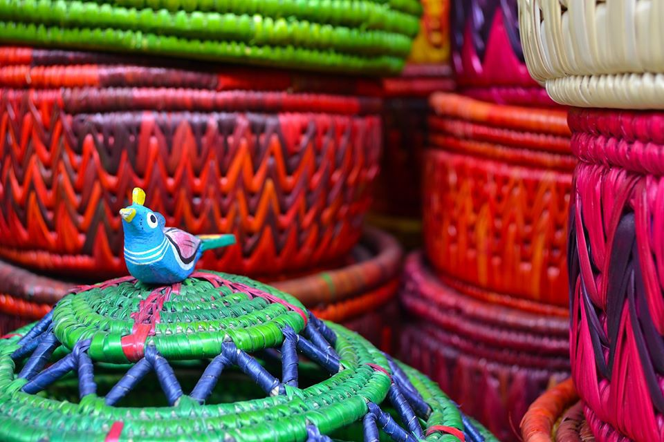 blue wooden bird resting on a colorful woven basket