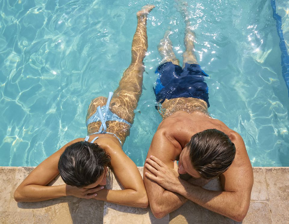 Hispanic couple relaxing in swimming pool
