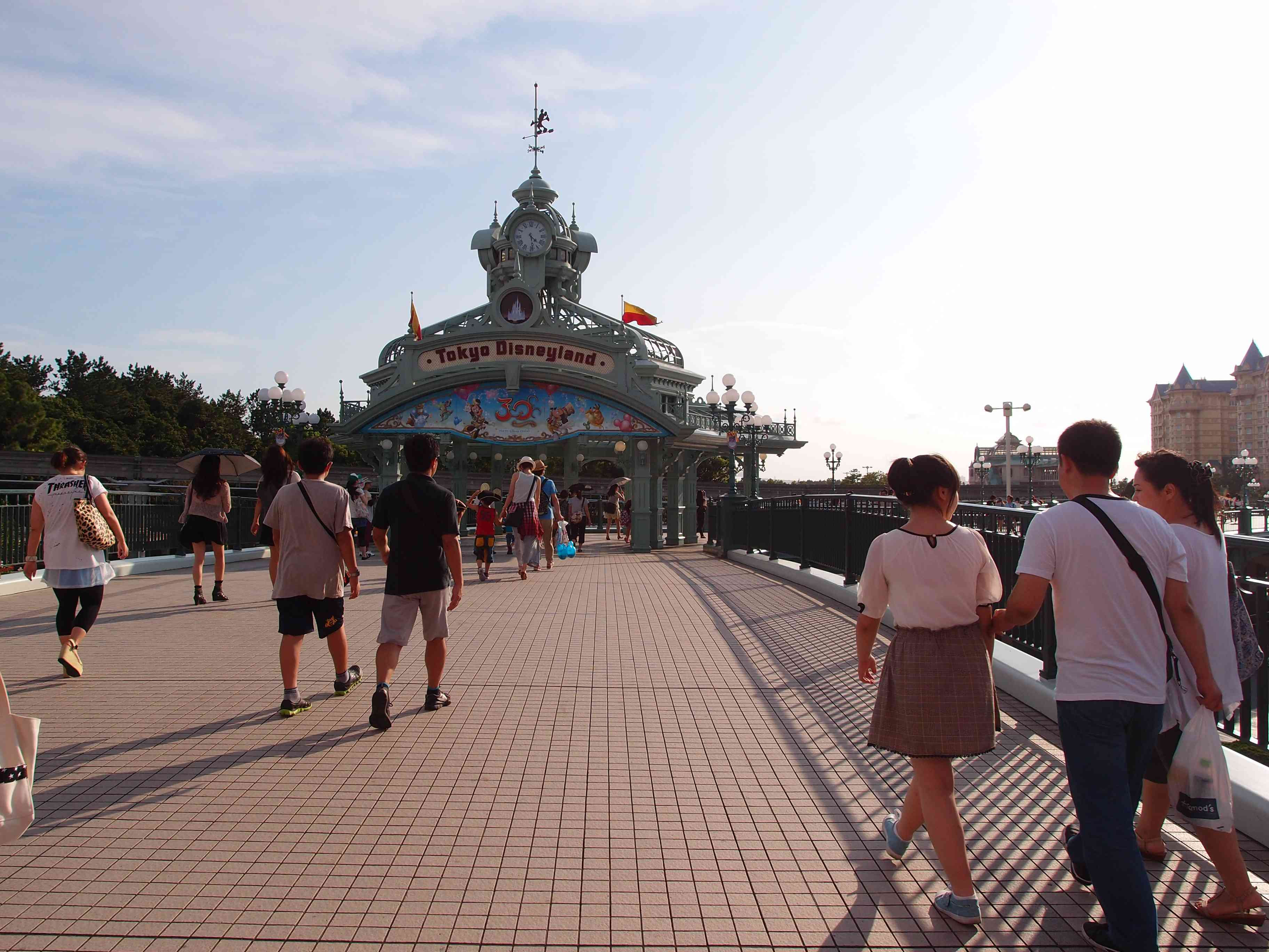 Entrance to tokyo disnetland with a group of people walking towards it