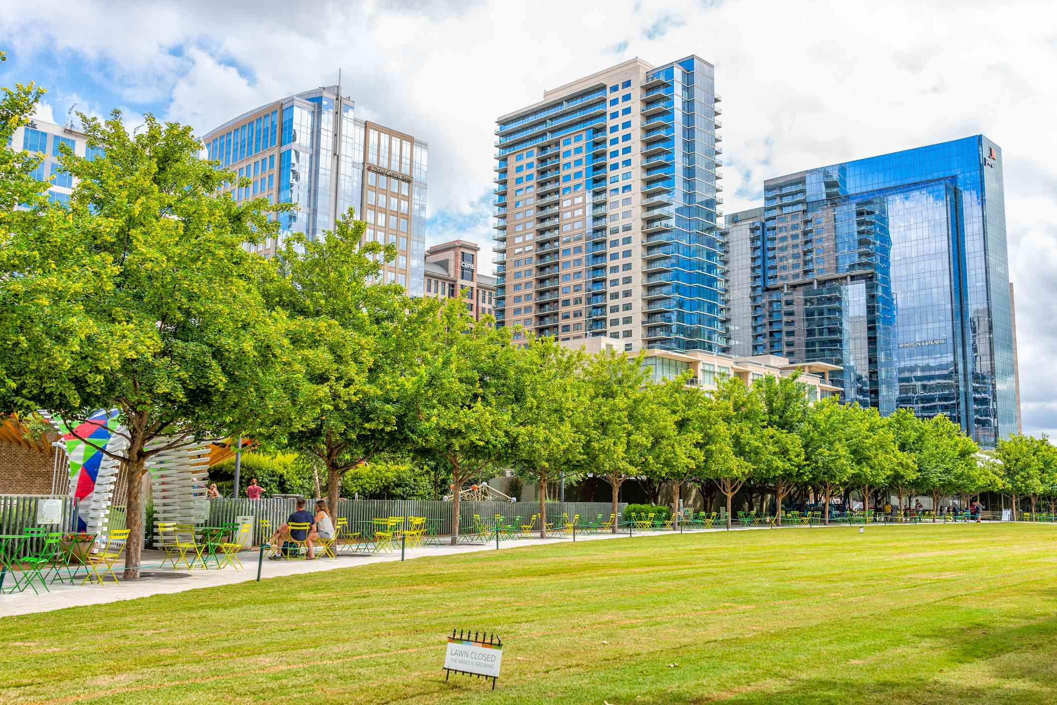 Downtown Klyde Warren green park in summer with lawn grass and cityscape skyline
