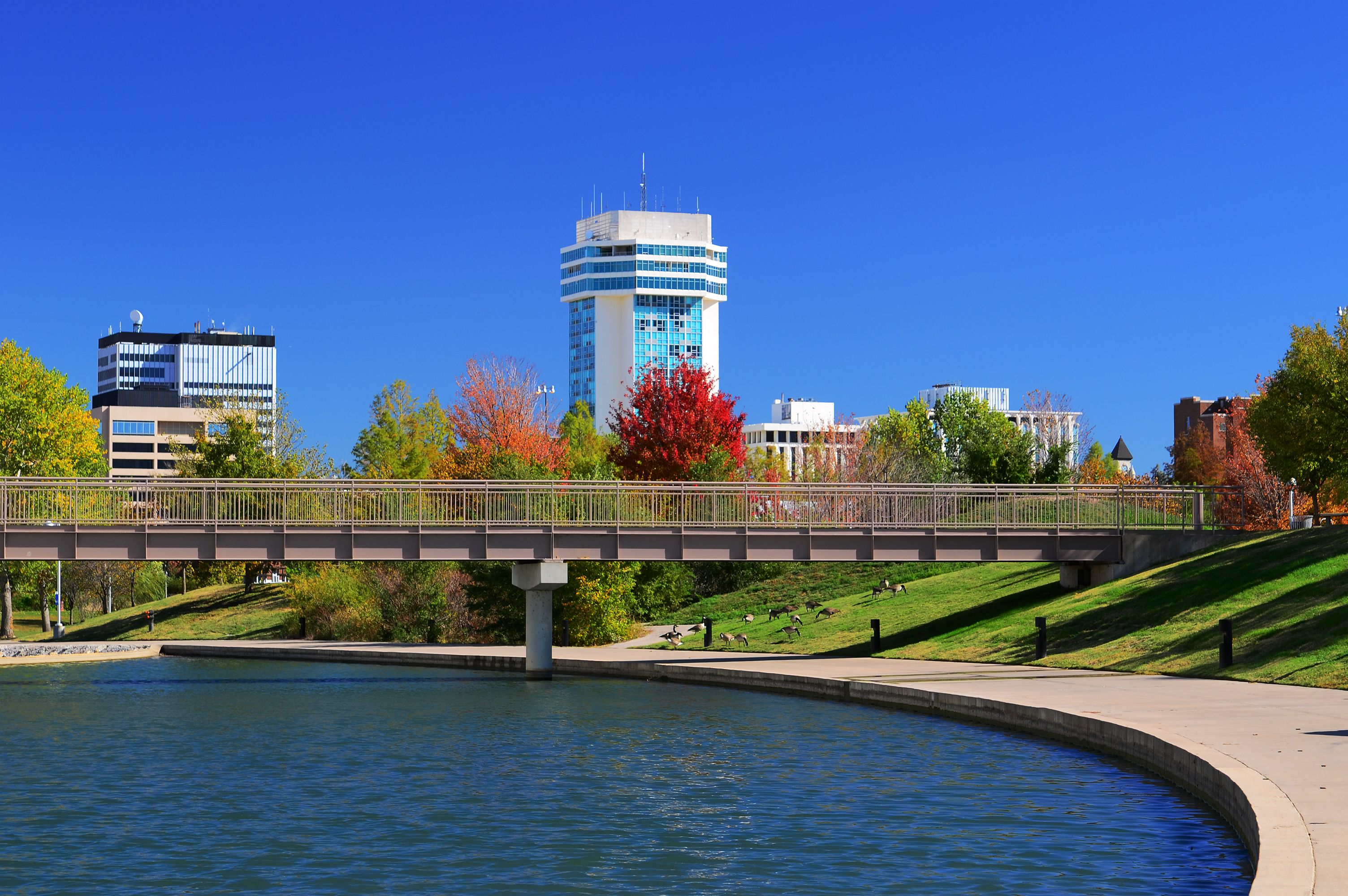 Downtown Wichita skyline with a waterway and park in foreground