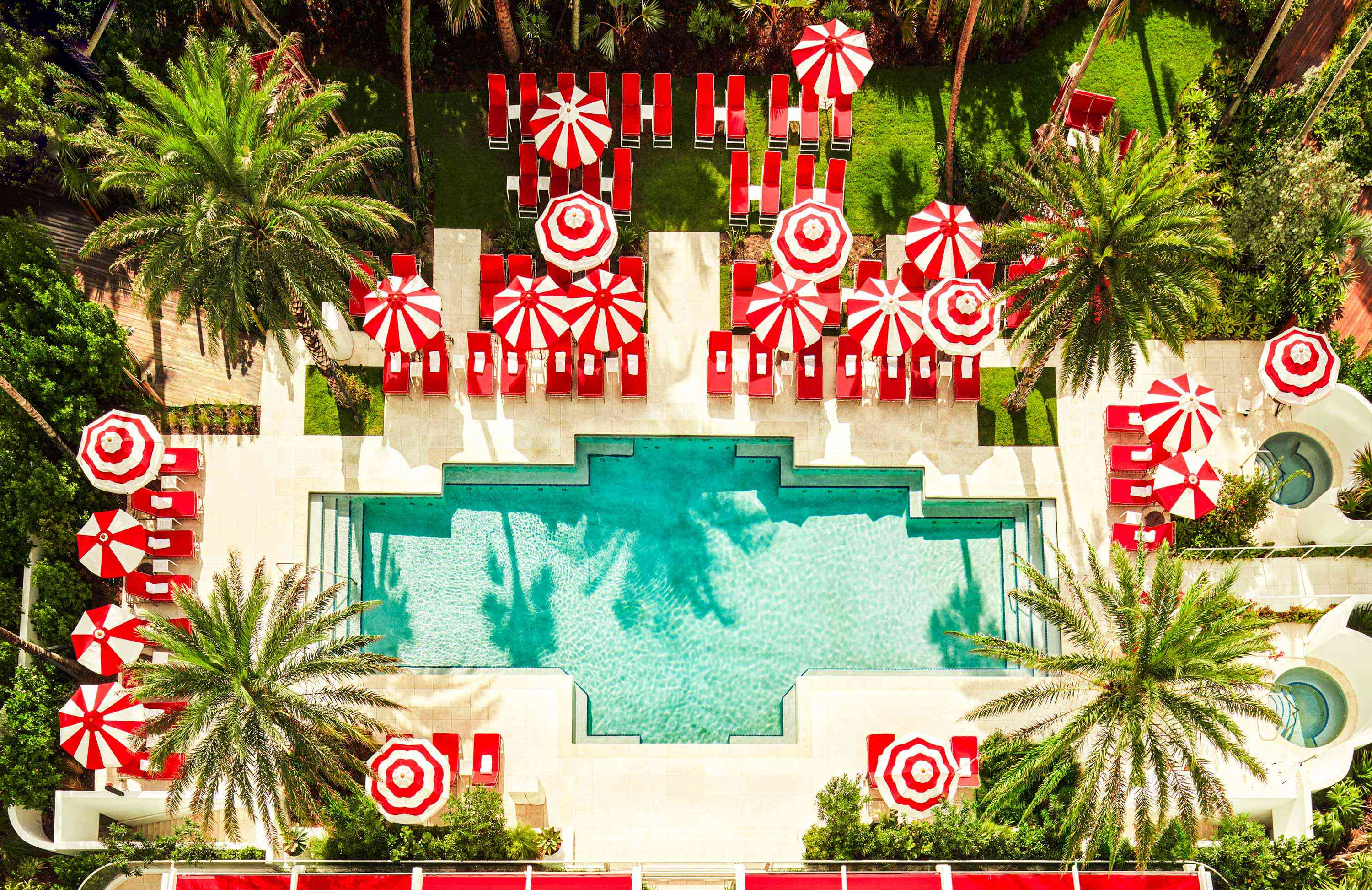 Aerial view of an outdoor pool with red lounge chairs and red and white umbrellas with varying patterns