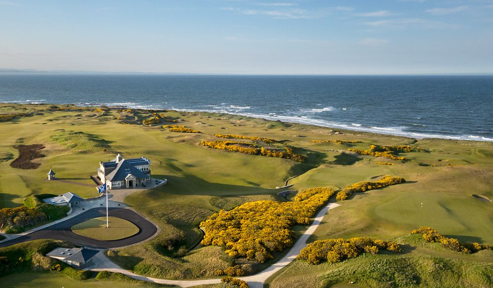 Aerial shot of a golf course in autumn next to the ocean