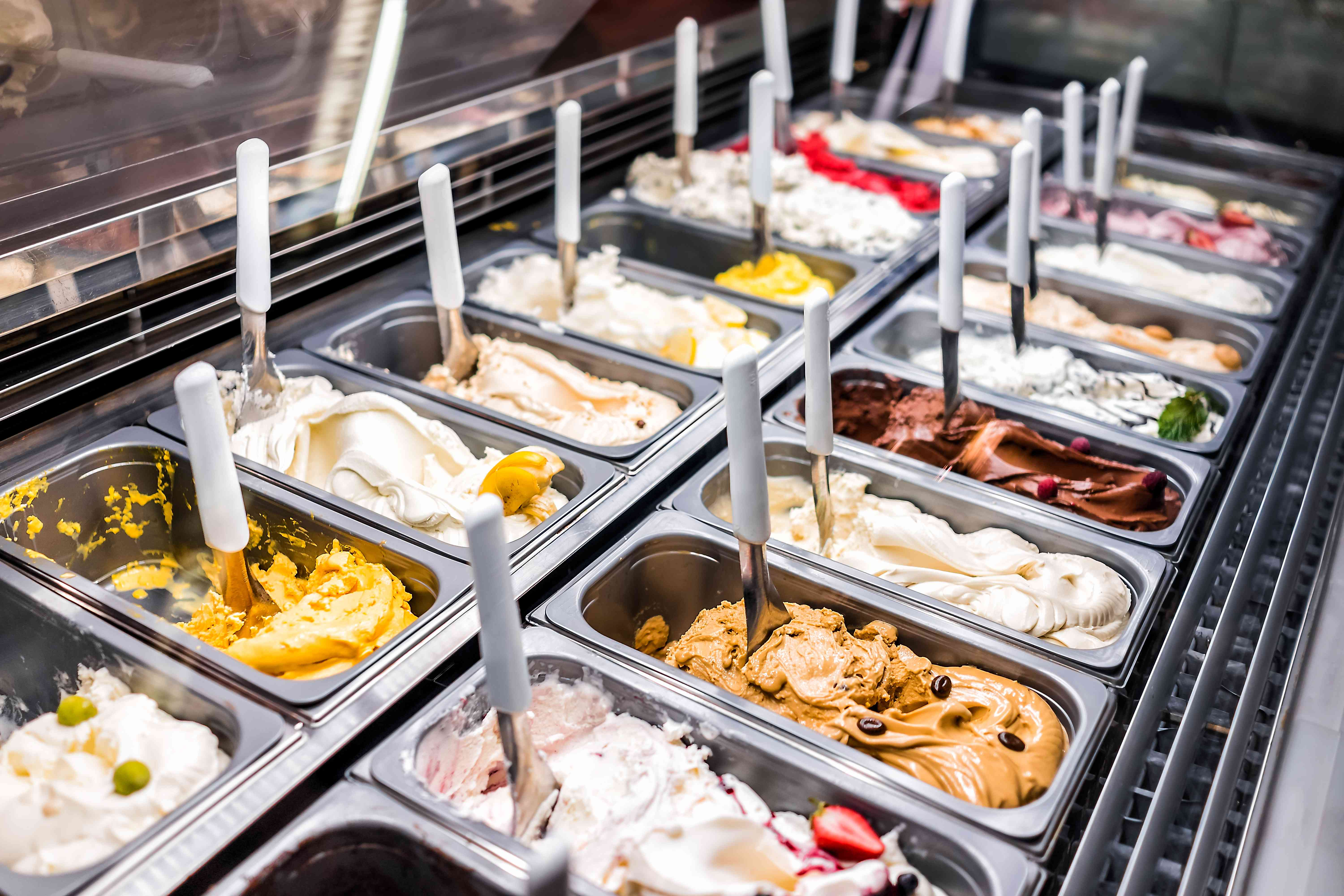 Ice cream frozen yogurt colorful serving counter parlour with many scoopable flavors, sorbet, chocolate, toppings, coffee