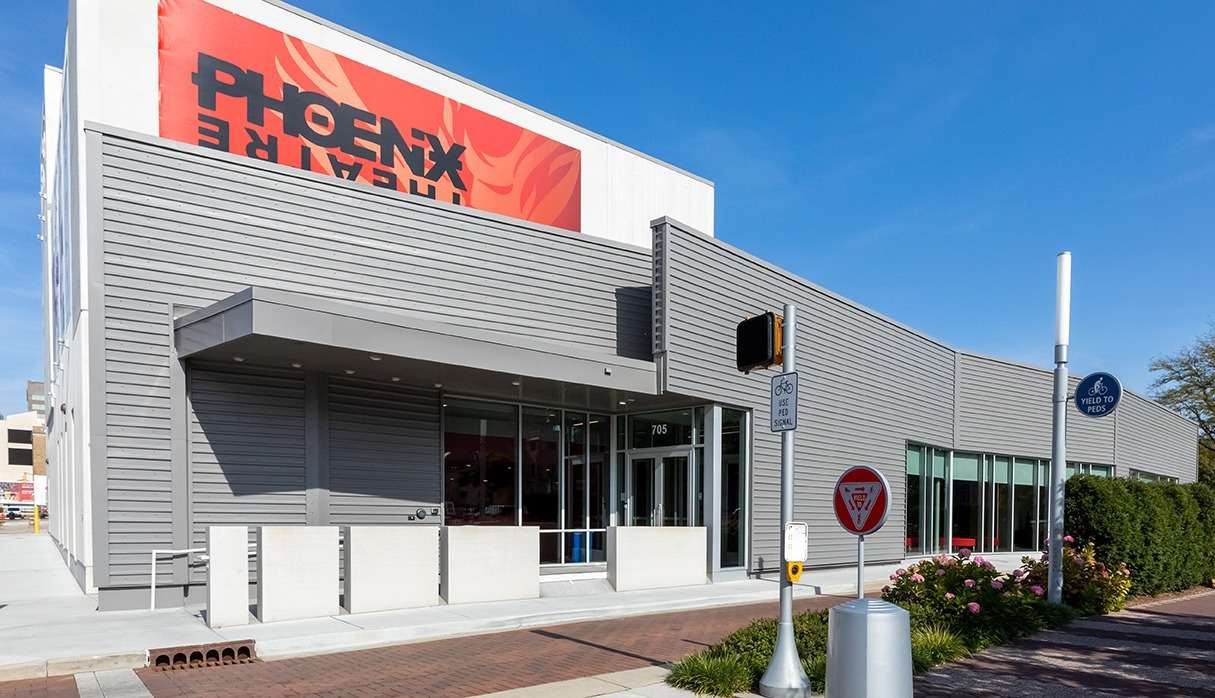 Gray modern exterior of the Phoenix Theater with a red sign displaying the business name
