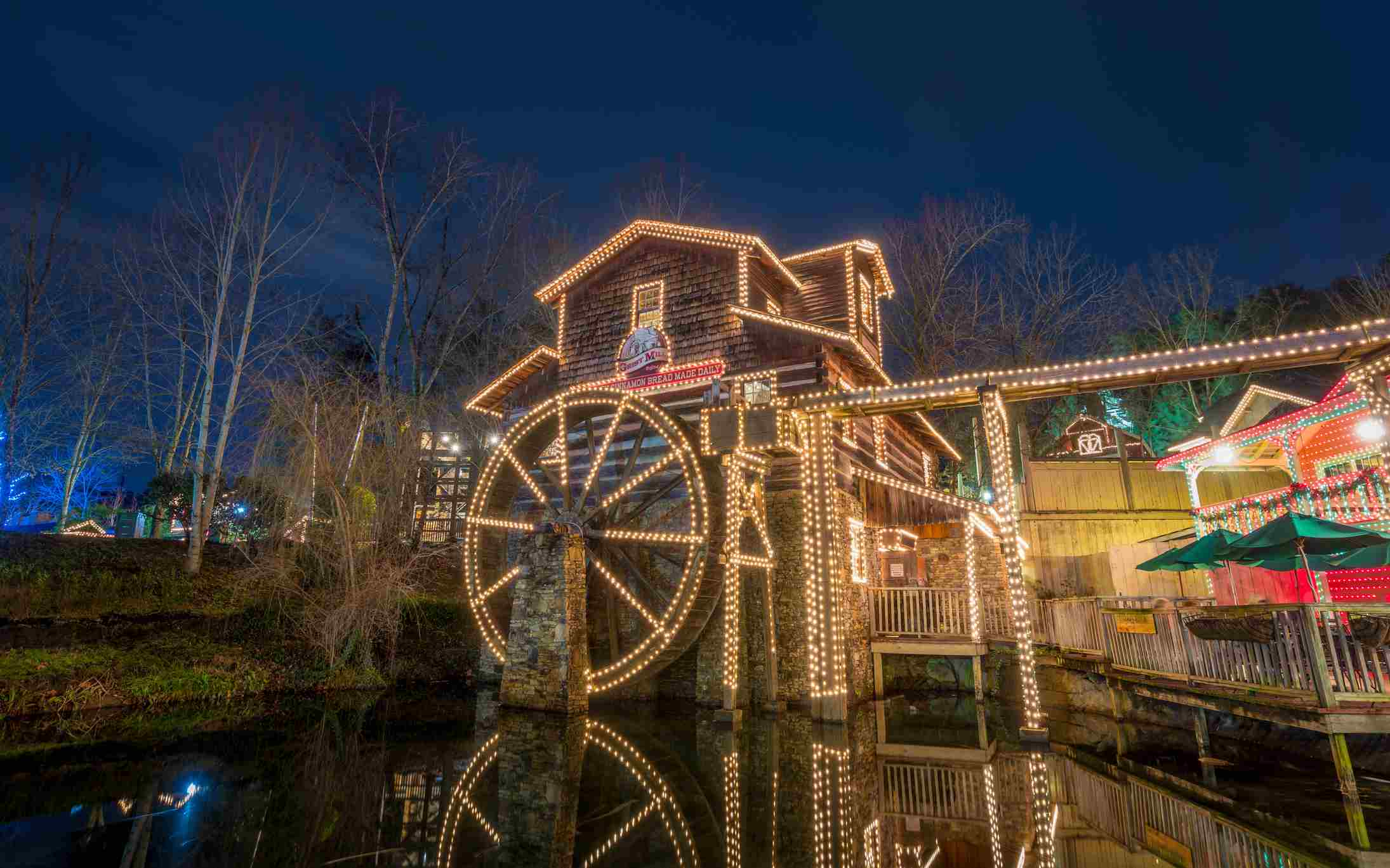 The Grist Mill at Dollywood a wooden watermill with a wheel with lights on it