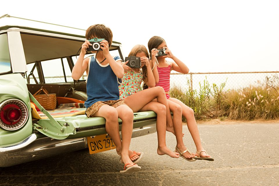 Three children sitting on the tailgate of a station wagon taking photographs