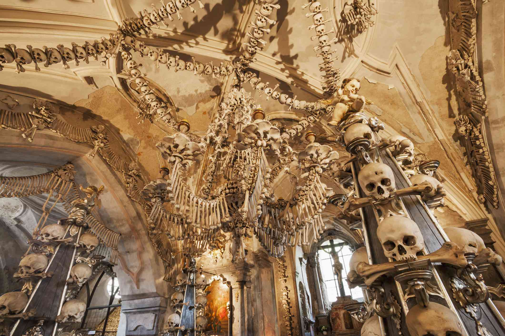 low angle of a vaulted cathedral ceiling decorated with hundreds of human skulls and long bones