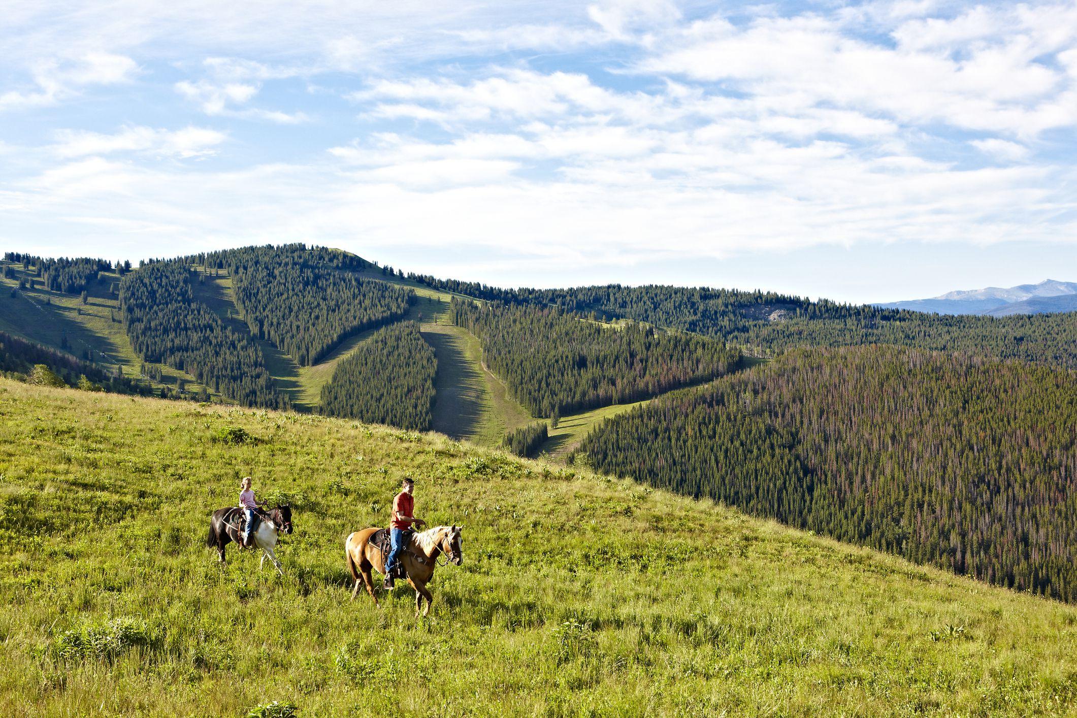 A cowboy races his horse across a Colorado ridge line.