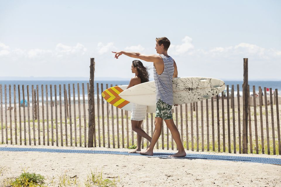Man pointing while walking with girlfriend by fence at beach