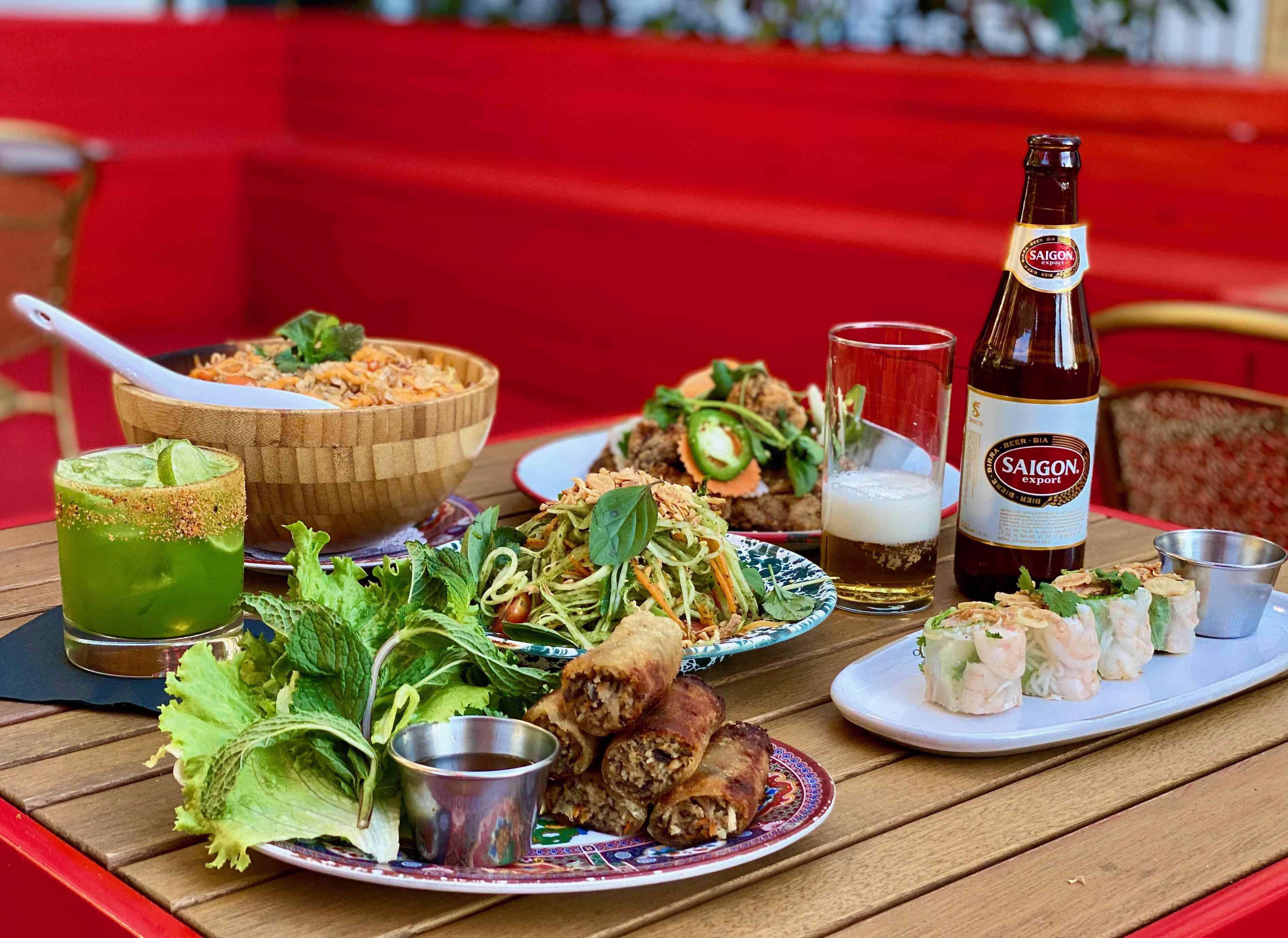 Dinner spread of Vietnamese-Cajun food including spring rolls, noodles, wraps, and Saigon beer