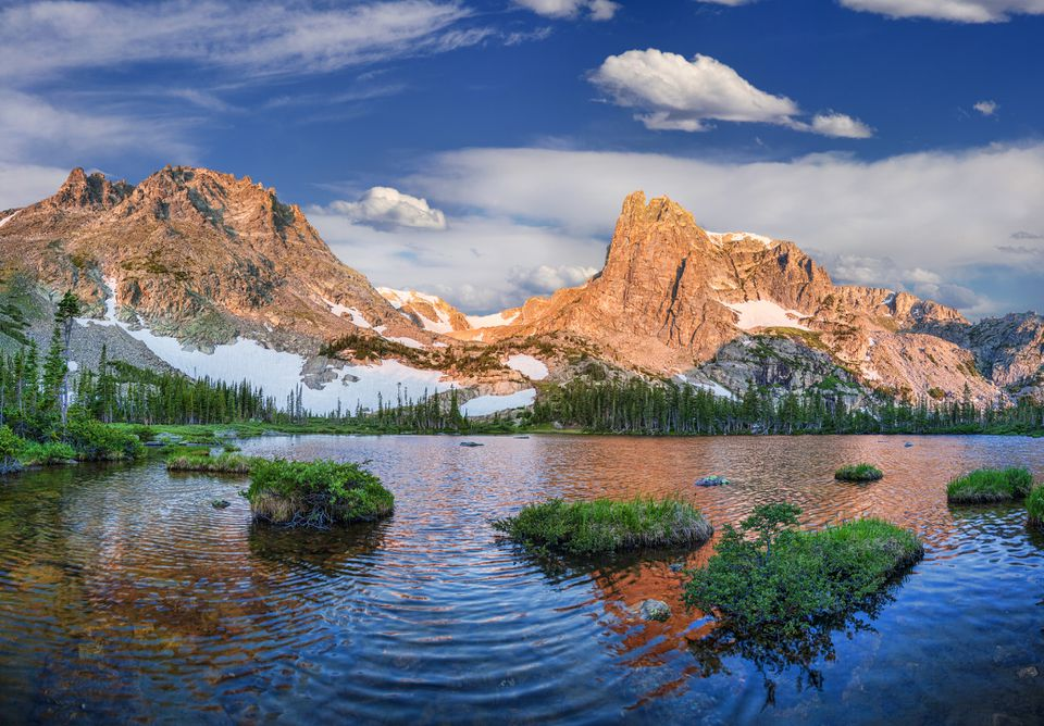rippling lake in rocky mountain national park with snow covered mountains in the distance