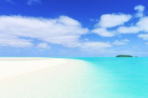 white sand beach with turquoise sea and blue sky with white clouds