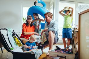 Happy family of five packing for holiday trip