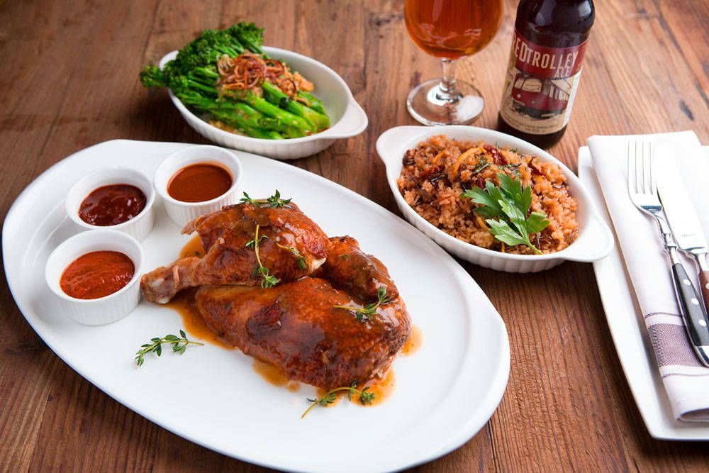 half rotisserie chicken with three dipping sauces on a plate. There's also a bowl of rice and a bowl of broccolini behind the plate of chicken