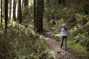 Female walking on trail through woods.