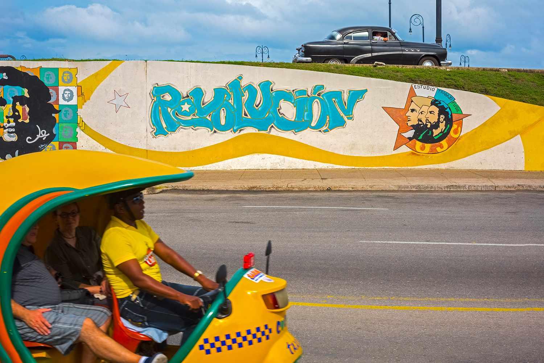 Cuba, Havana, Revolucion Mural and yellow Coco Taxi