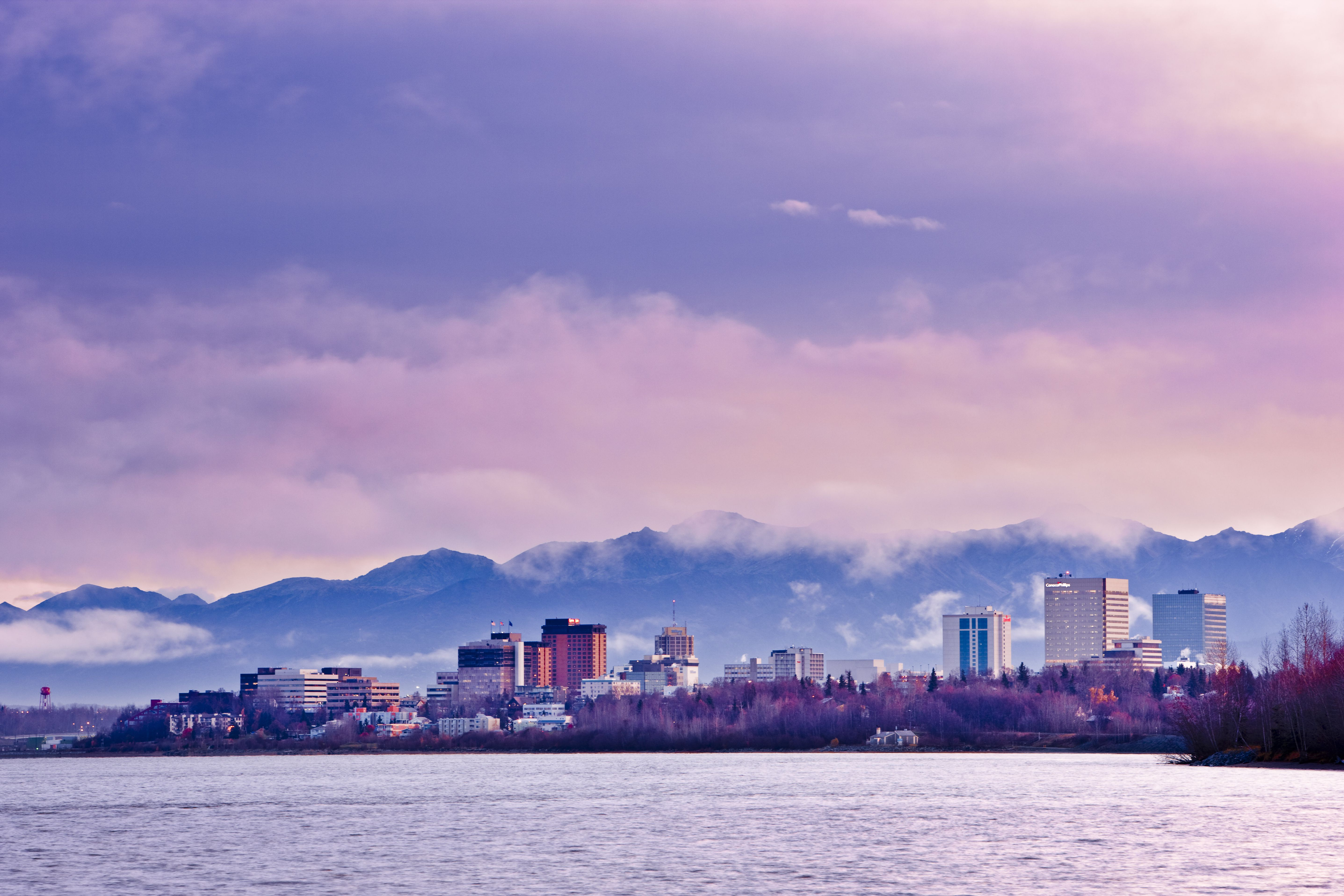Anchorage skyline on the water beneath a wall of mountains.
