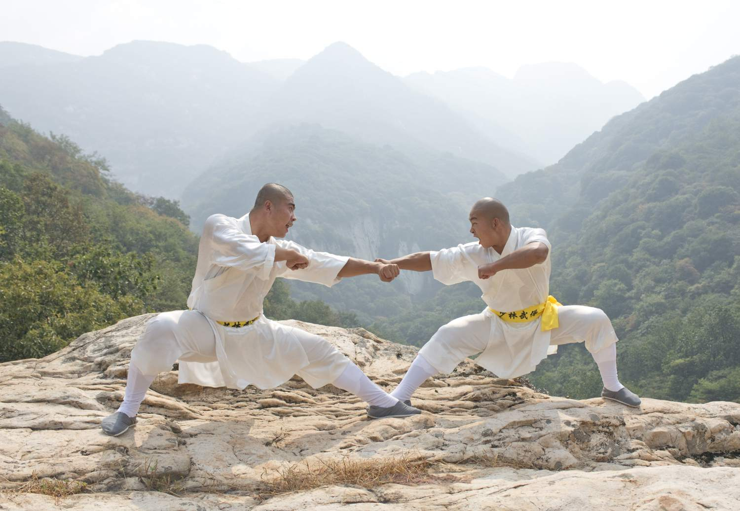Shaolin monks practice Kung Fu on a rocky overlook near Mt. Song, China