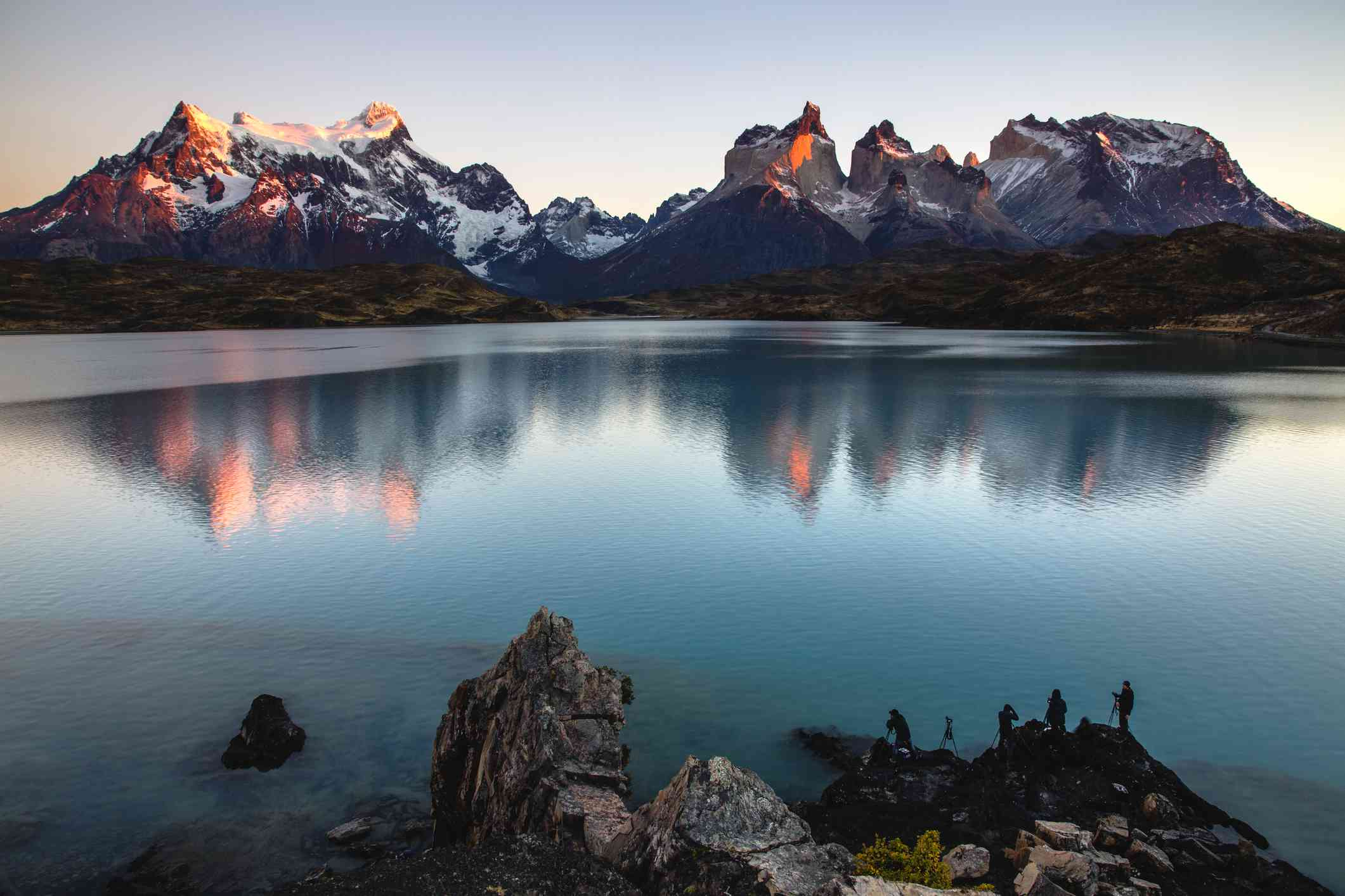 The majestic peaks and spires of Torres del Paine reflected on a blue lake at dawn, Torres del Paine, Chile, South America.