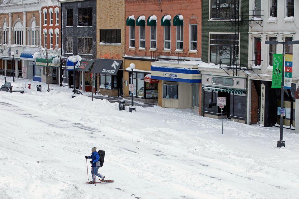 Un hombre usa raquetas de nieve para moverse por el centro de la ciudad, cerca de la Universidad de Iowa, mientras una gran tormenta de invierno atraviesa el Medio Oeste el 2 de febrero de 2011 en Iow