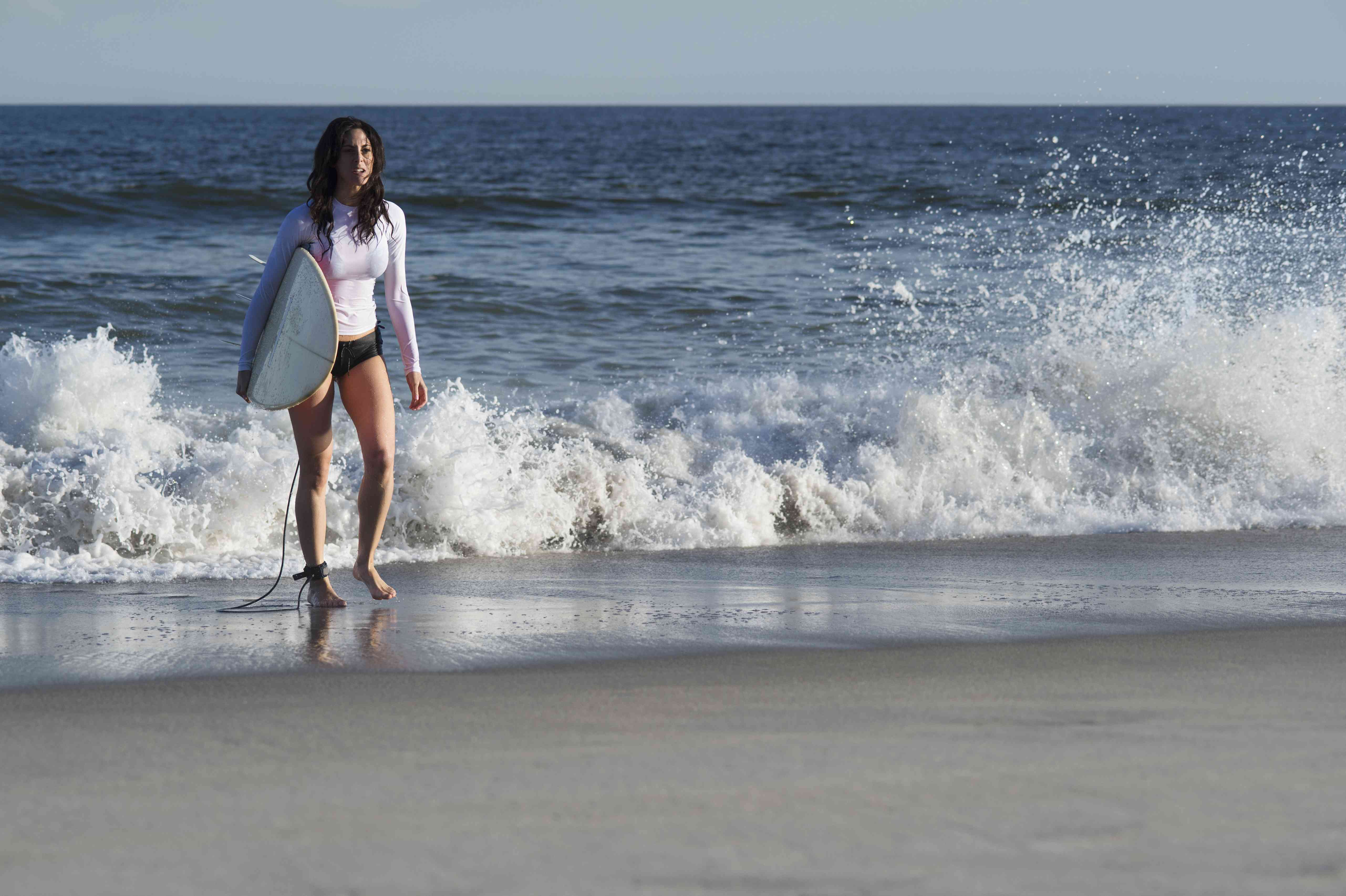 USA, New York State, Rockaway Beach, Woman carrying surfboard on beach