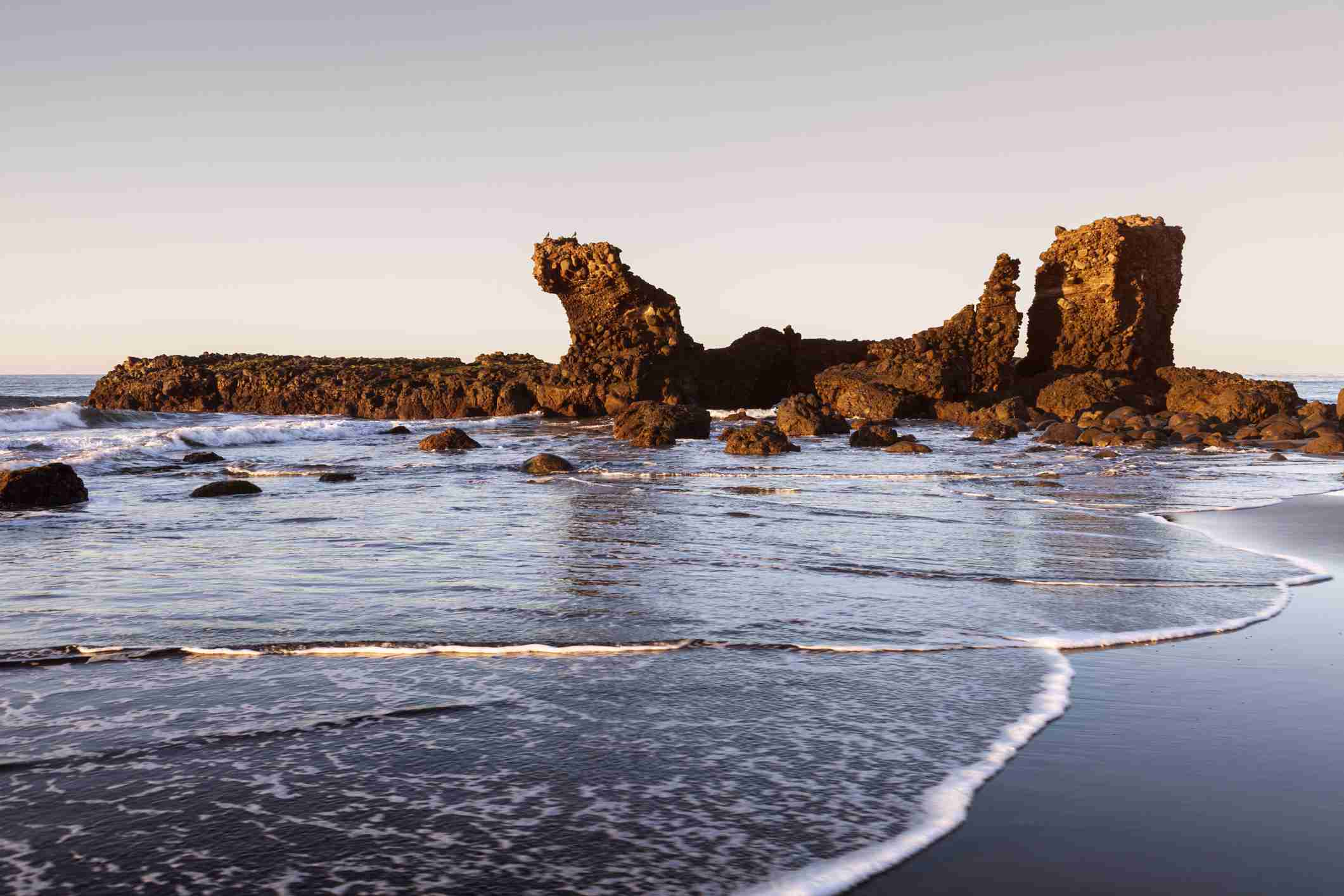 Black sand beach with rock formations in the background at El Tunco Beach