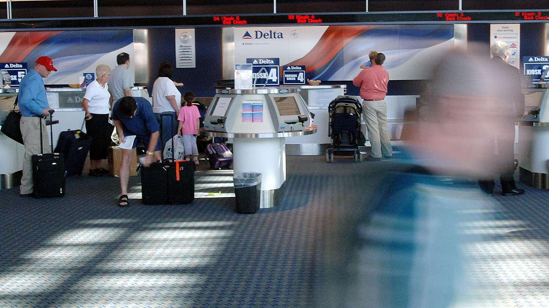 Unidentified passengers make their way pass the Delta ticket counter at Cincinnati/Northern Kentucky International Airport