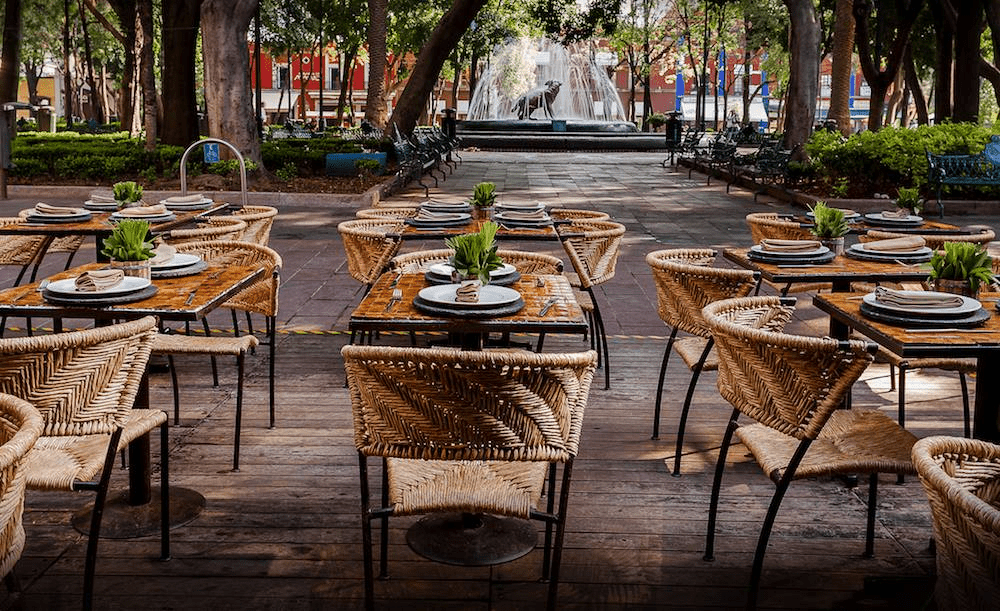 Wicker chairs and wooden tables from Los Danzantes on a patio overlooking a main square in Mexico City