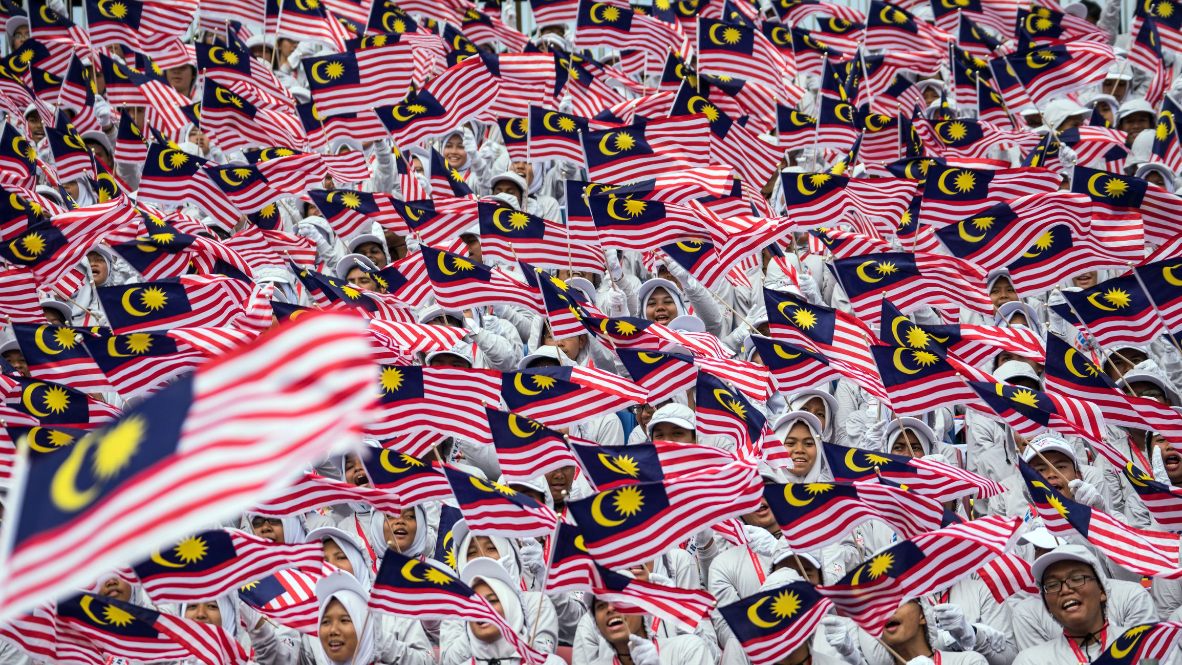 People waving Malaysian flags during Merdeka parade